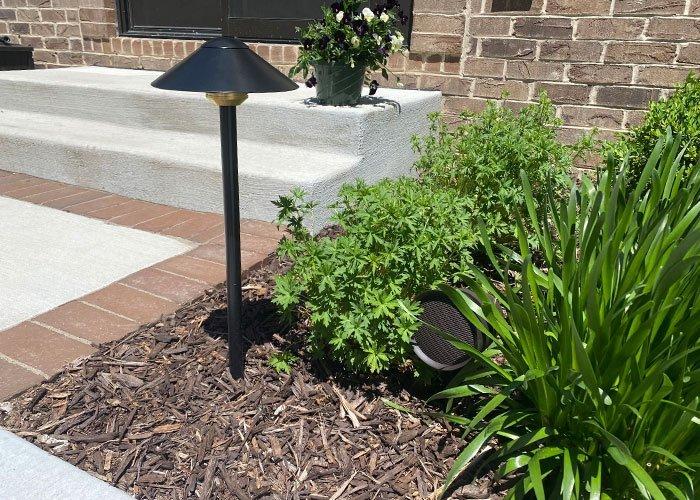 landscape sound speaker hidden in plants next to outdoor lighting fixture by house front door and brick walkway