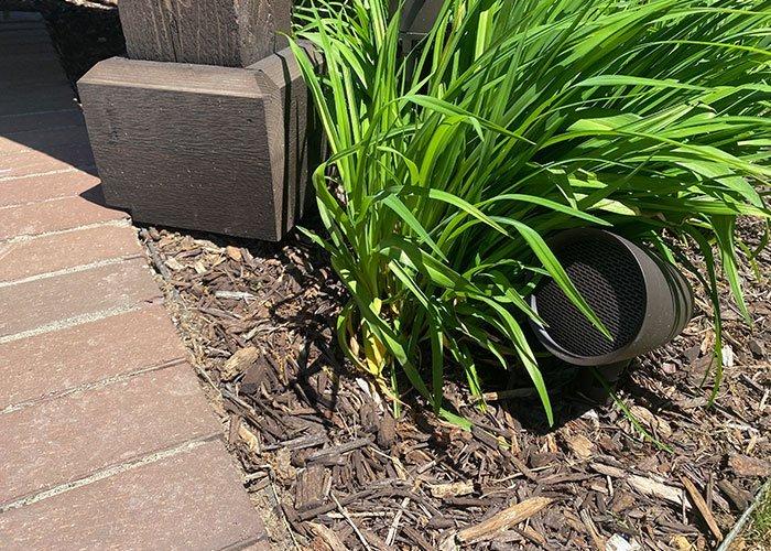 outdoor audio speaker next to pergola and brick patio